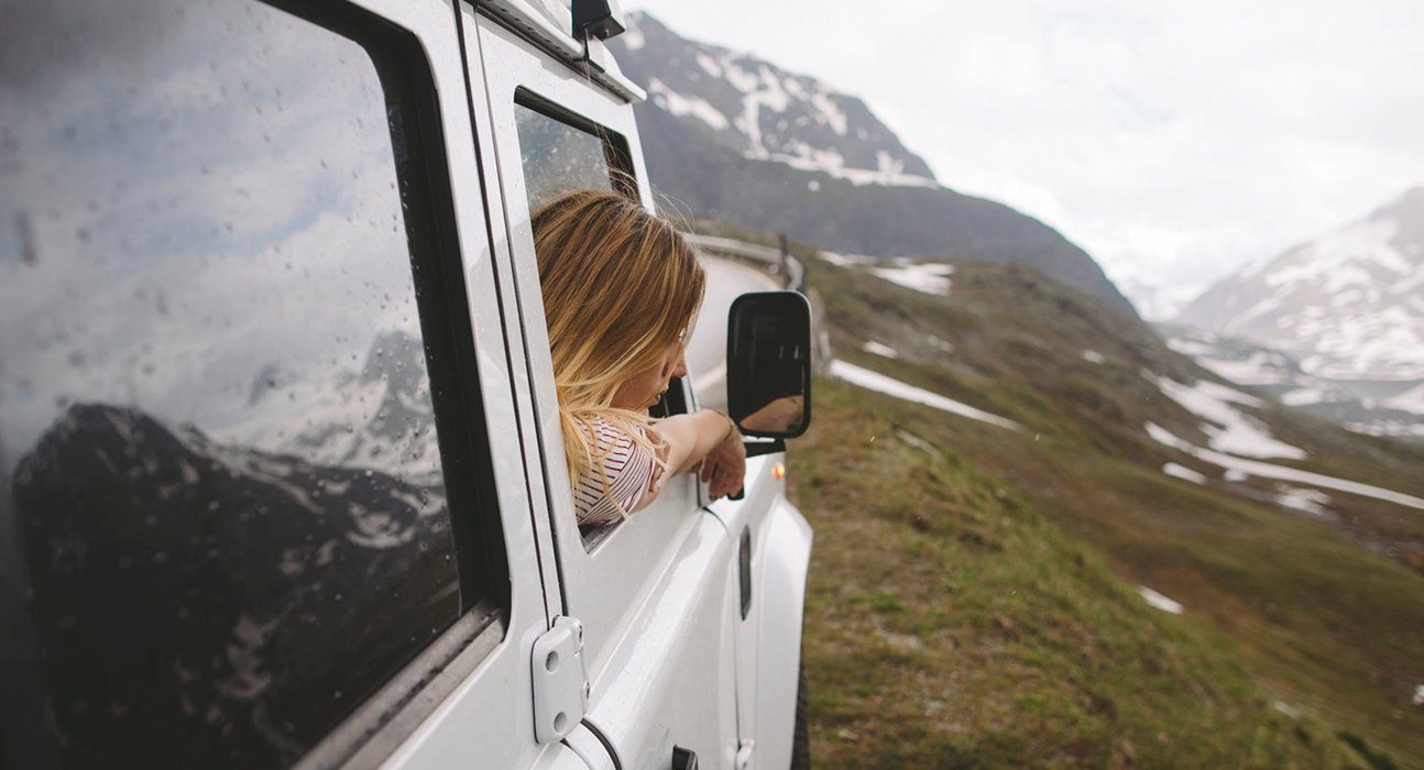 A woman looking out the window of her white Jeep at snow covered mountains