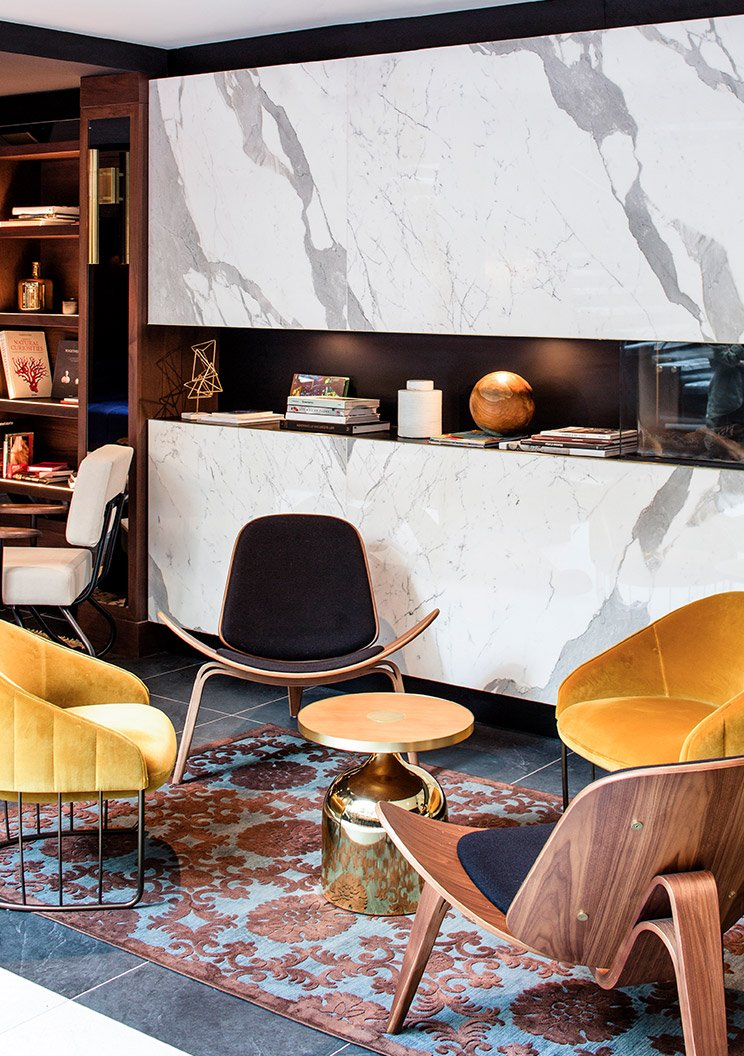 A Groupe Antonopoulos hotel lobby area with modern furniture including yellow suede armchairs