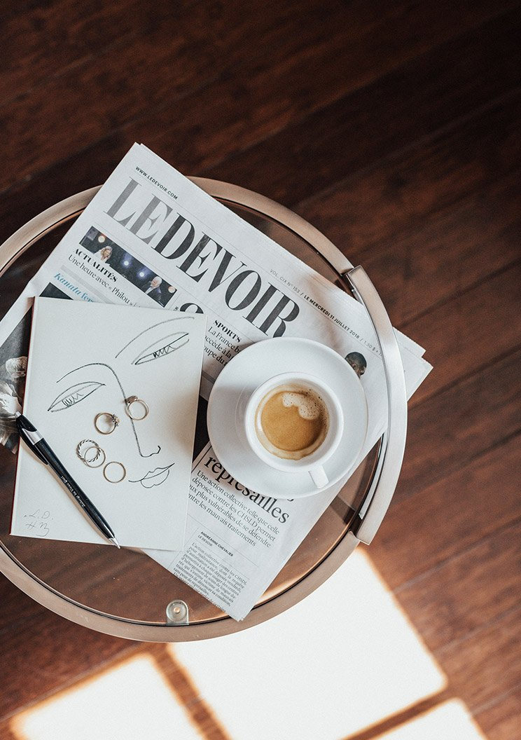 A coffee left on top of a newspaper on a small table beside some jewellery.