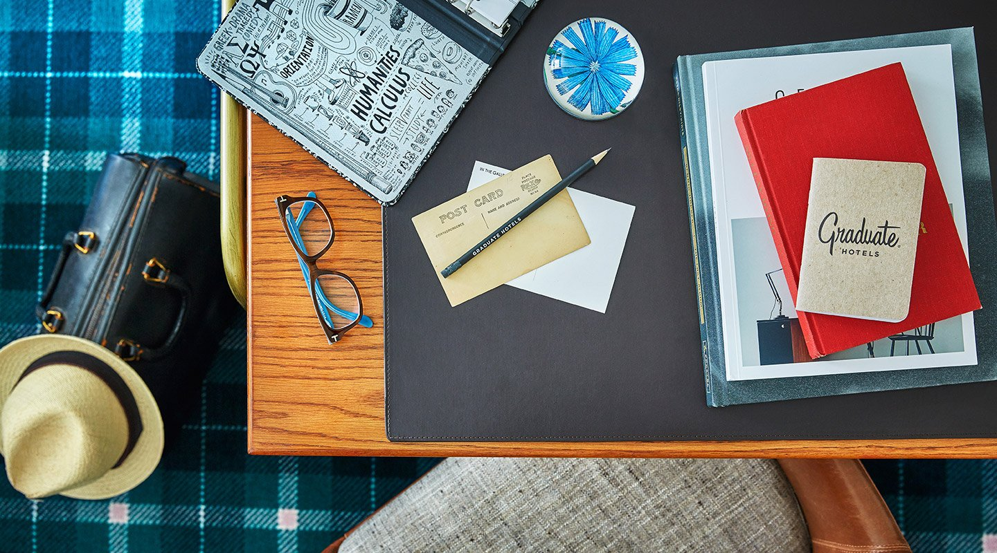 Graduate hotel stationery on a desk. Taller image.