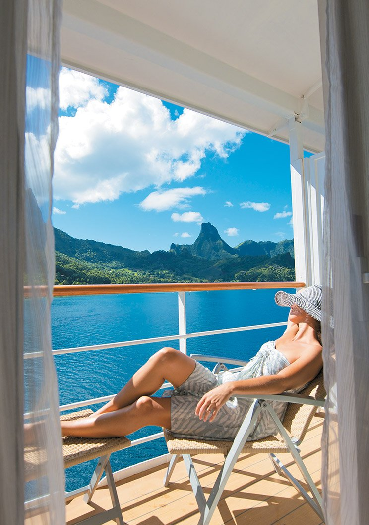 A woman sunbathing on a wicker chair on the balcony of her room aboard a Paul Gauguin cruise liner