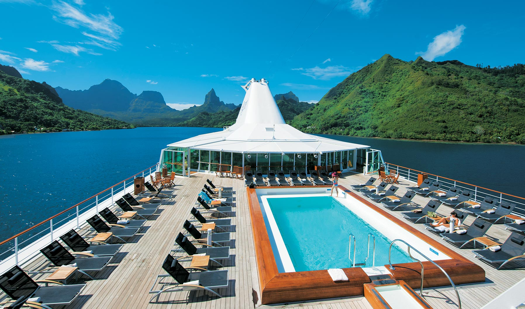 The pool on the top of a Paul Gauguin cruise liner cruising near lush green islands