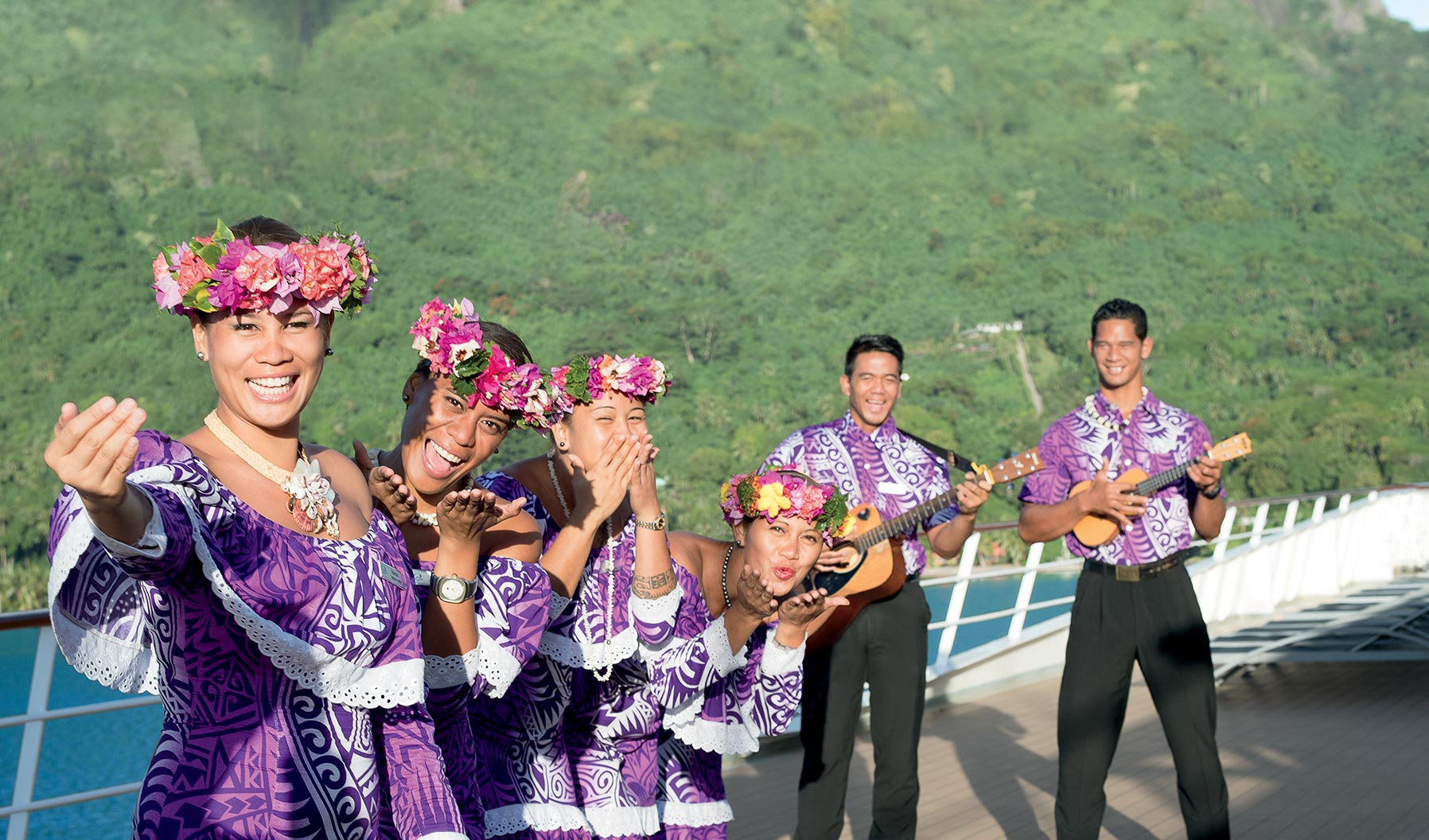 4 women and 2 men ready to welcome Paul Gauguin guests in purple dresses and shirt with flower crowns and musical instruments