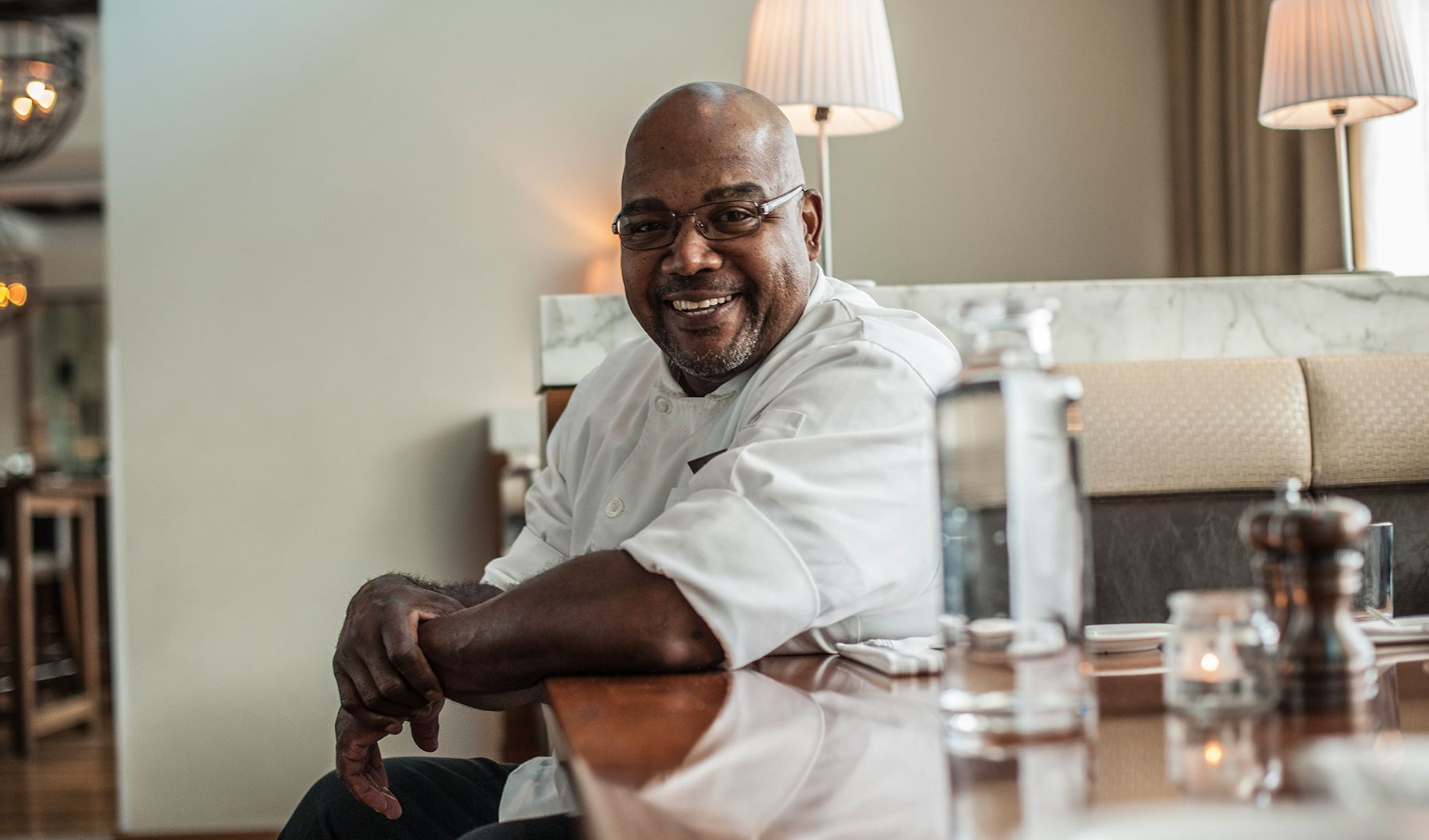 A chef smiling at the camera while sat at a restaurant booth table.