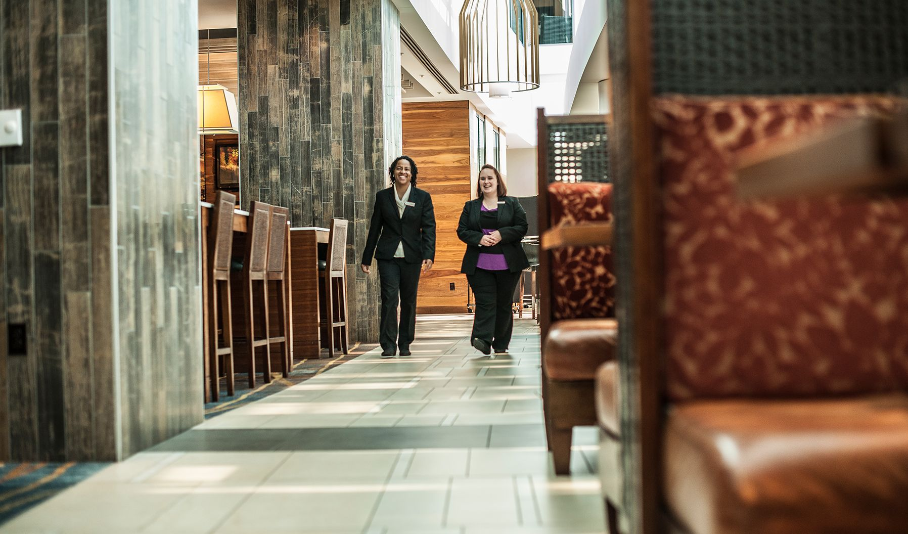 Two female members of staff walking through a White Lodging managed hotel.