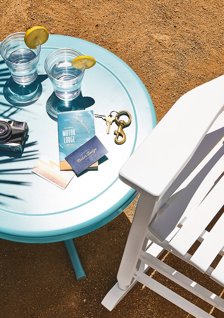 Motor Lodge hotel leaflets and business card on a table beside a deck chair on the beach