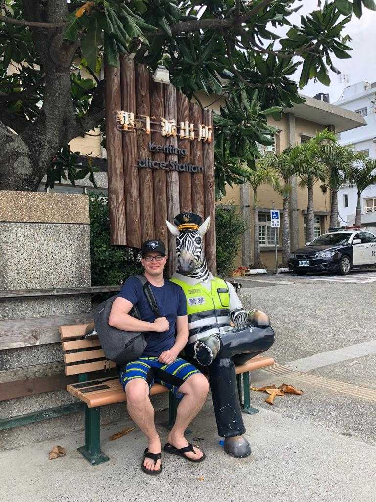 guy sitting on bench next to a statue zebra dressed as a police officer