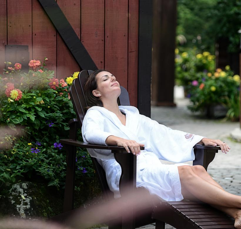 Female guest lounging outdoors at the Scandinave Spa