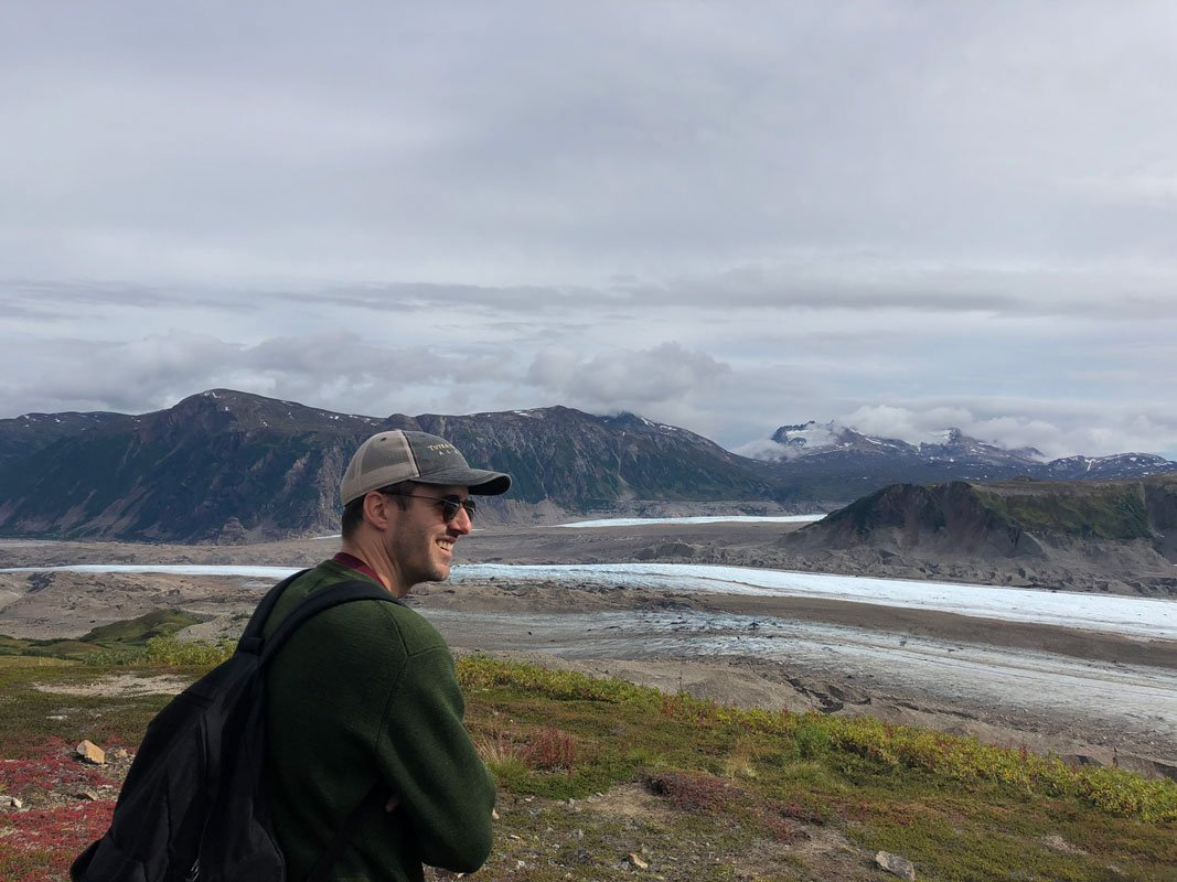 A man smiling and surrounded by mountains
