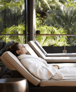 Woman relaxing on a spa lounger at a Miraval hotel